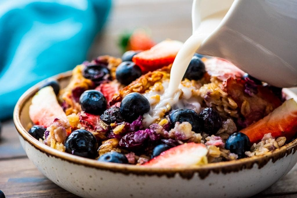 Bowl with berry baked oatmeal with a white ceramic pitcher pouring milk onto it.