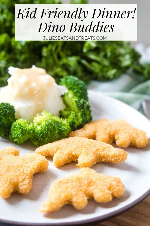 Dino chicken nuggets, mashed potatoes, gravy, and broccoli on a white plate