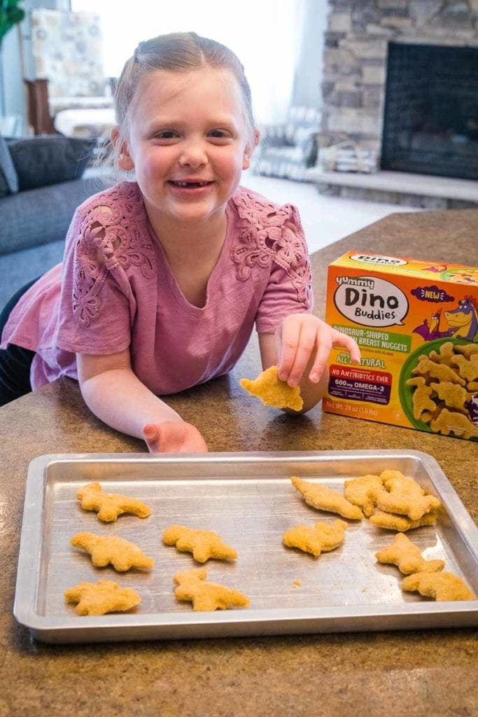 Child with dino buddies chicken nuggets on pan