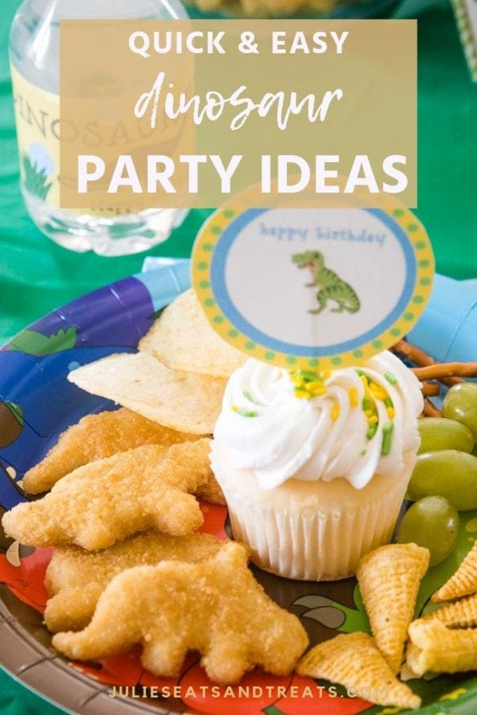 Dinosaur happy birthday sign in a vanilla cupcake on a plate with dino chicken nuggets, potato chips, bugels, and grapes