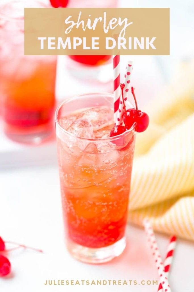 Shirley temple drink in a tall glass with cherries and two straws