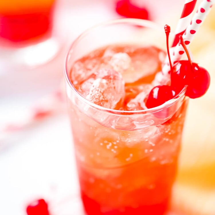 Tall Glass of Shirley Temple with cherries and two straws