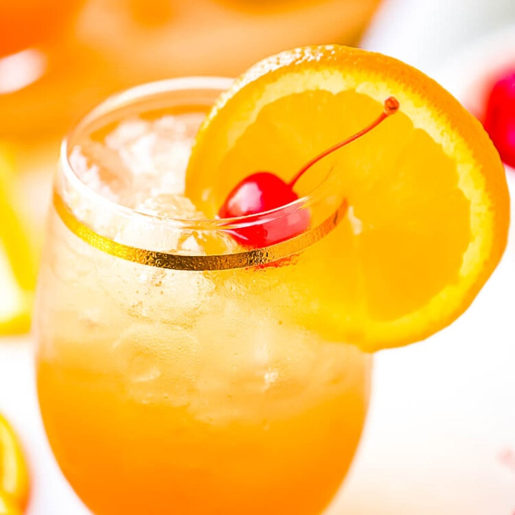 Glass of Amaretto Sour Drink with an orange slice and cherry