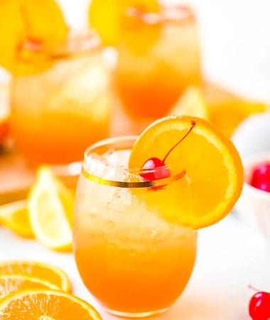 Amaretto Sour prepared in glass with an orange slice and cherry
