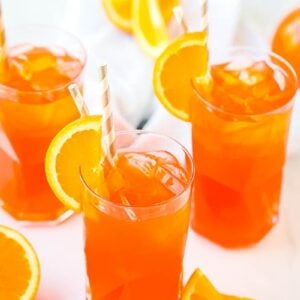 Three glasses of Aperol Spritz with orange slices