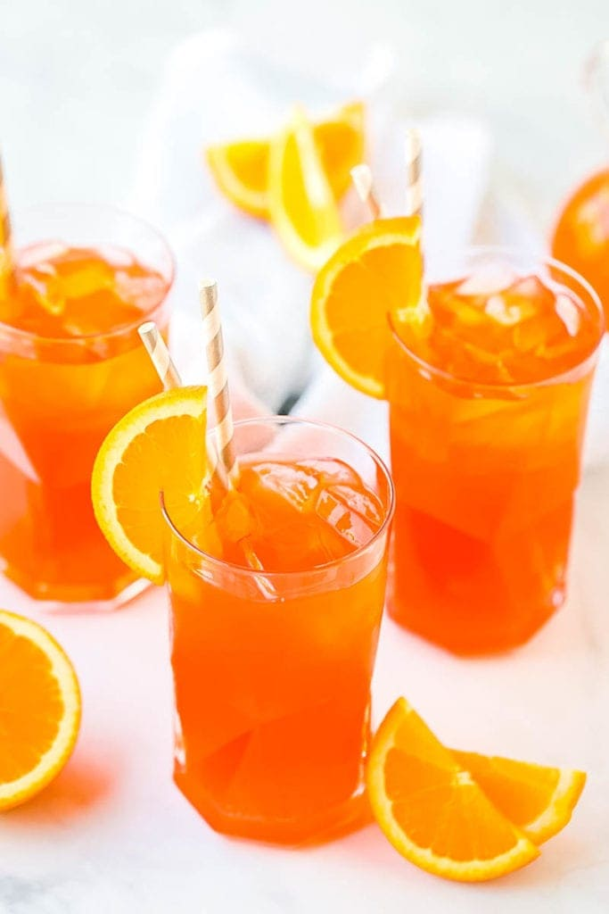Marble background with Cocktail glasses full of Aperol Spritz garnished with a slice of orange and gray and white paper straws