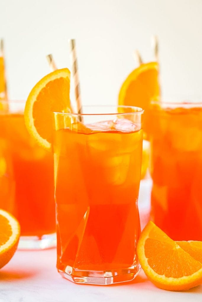 Close up image of an Aperol Spritz in tall glass with two in the background. Orange slices on marble surface next to glasses.