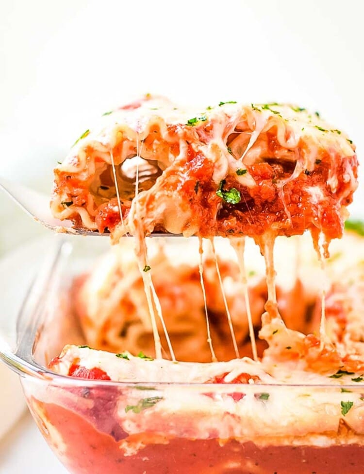 Spatula with Lasagna Roll Up on it lifting out of casserole with cheese pull