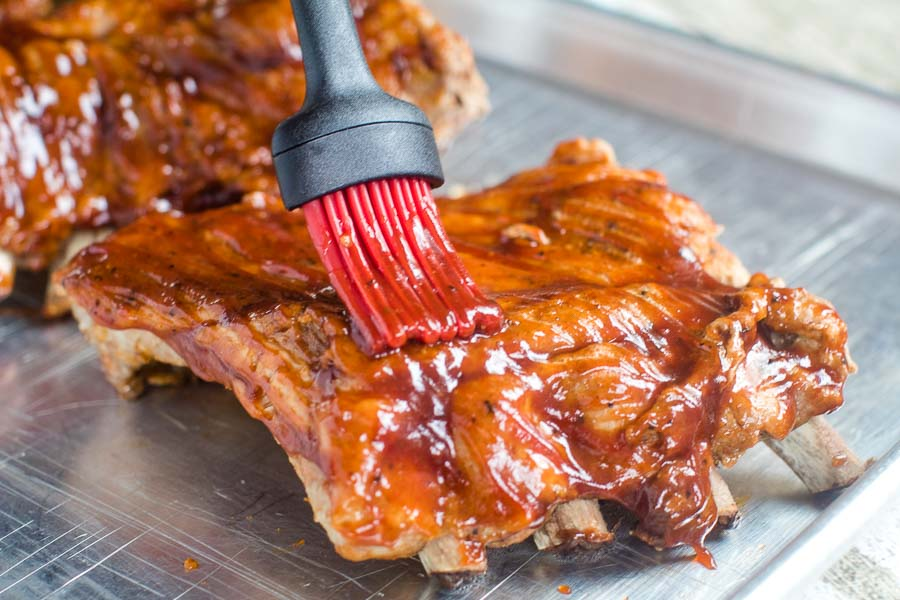 Instant Pot Baby Back Ribs being brushed with sauce