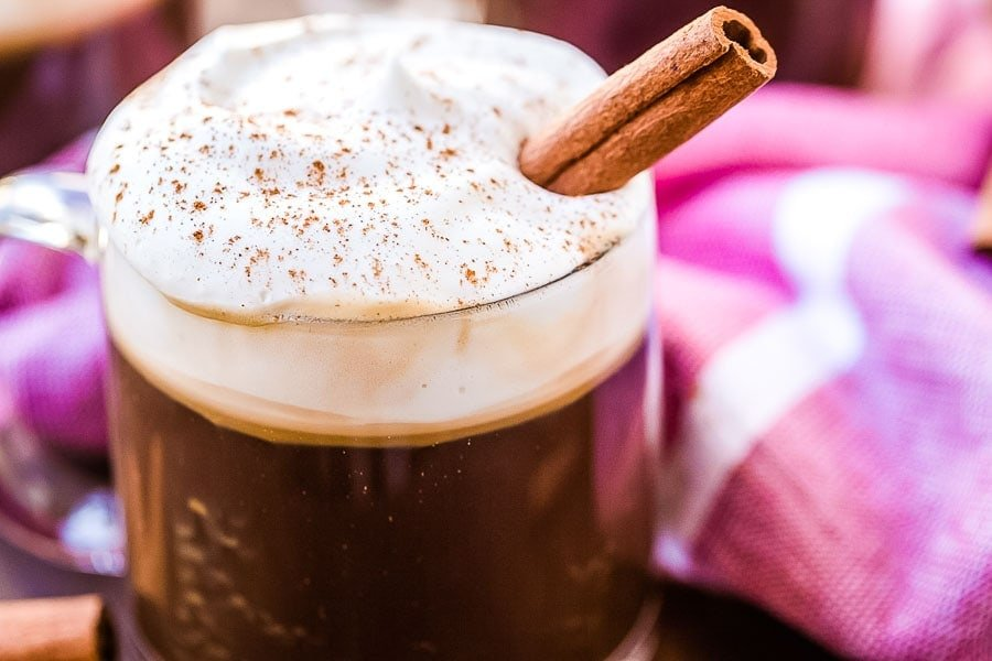 Mug of Irish Coffee topped with whipped cream, cinnamon and a cinnamon stick