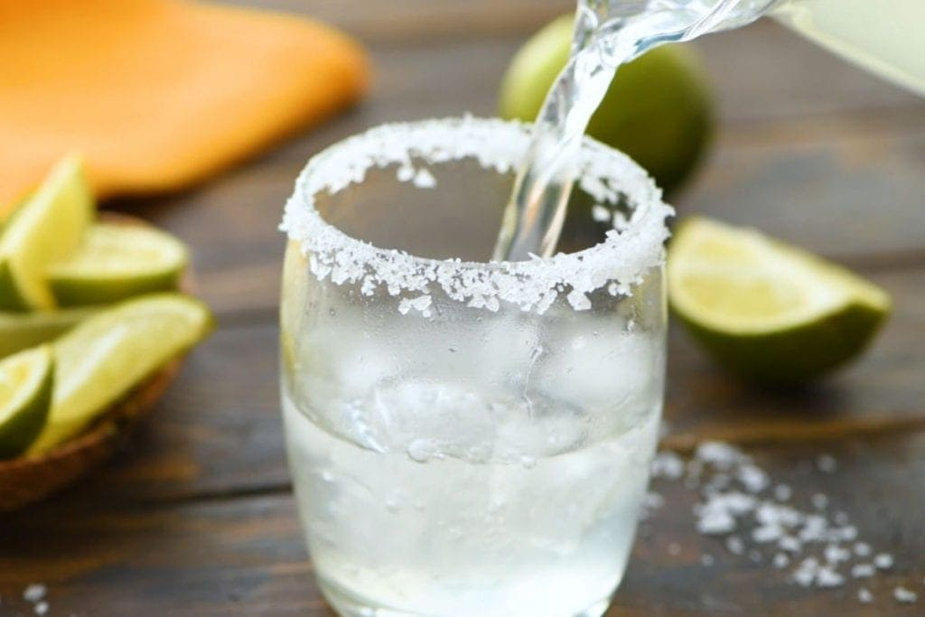 Pouring Margarita out of a glass pitcher and into a glass that's rimmed with salt.