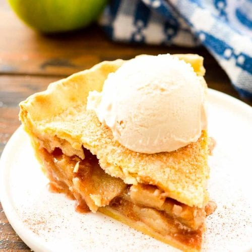 Slice of Apple Pie topped with a scoop of vanilla ice cream