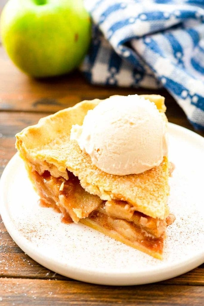Slice of Apple Pie topped with ice cream on a white plate with blue and white napkin in background and a green apple.