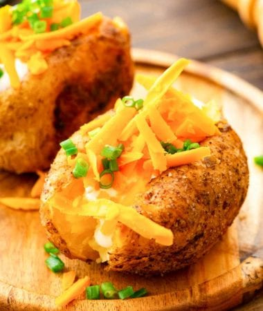 Baked Potatoes topped with shredded cheese on cutting board