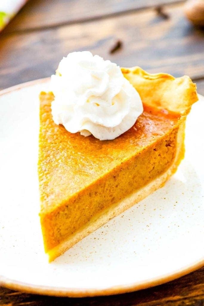 Pumpkin Pie slice on white plate with a dallop of whipped cream on top.