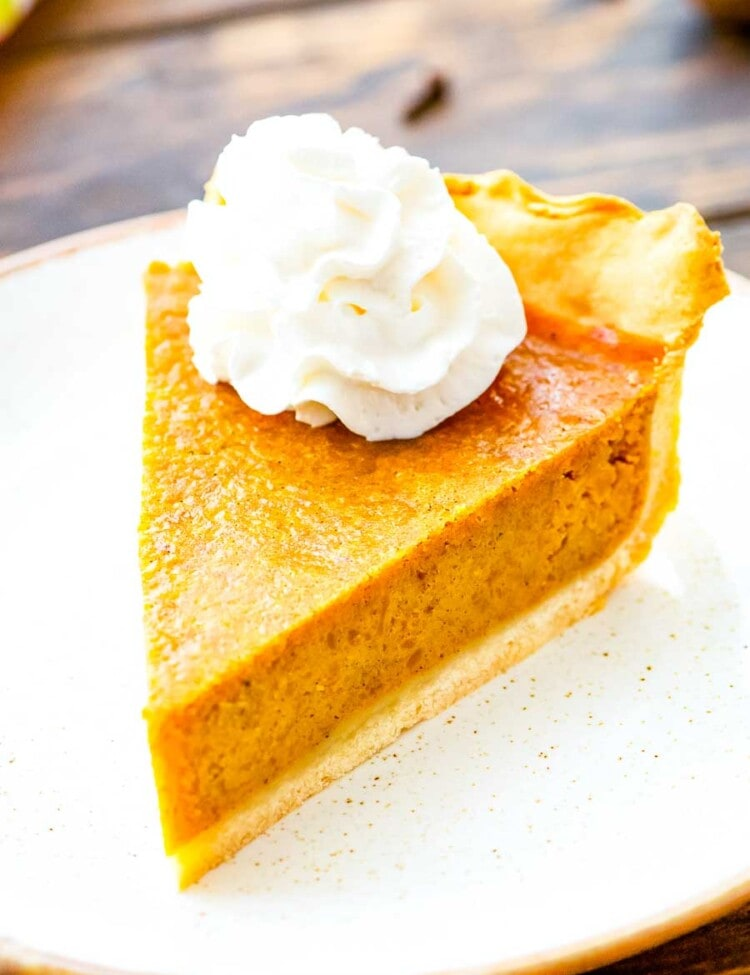 Pumpkin Pie slice topped with whipped cream on a white plate