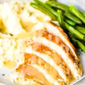 Slices of turkey, mashed potatoes, green beans, and gravy on a plate