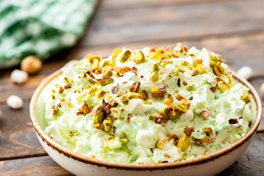 Pottery bowl of watergate salad topped with chopped pistachios on a wooden background