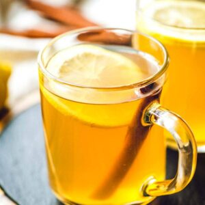 Glass mugs of Hot Toddy with lemon slices and cinnamon sticks