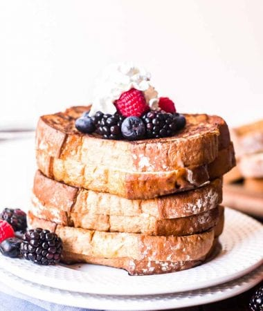 Stack of stuffed french toast topped with whipped cream and berries on a plate