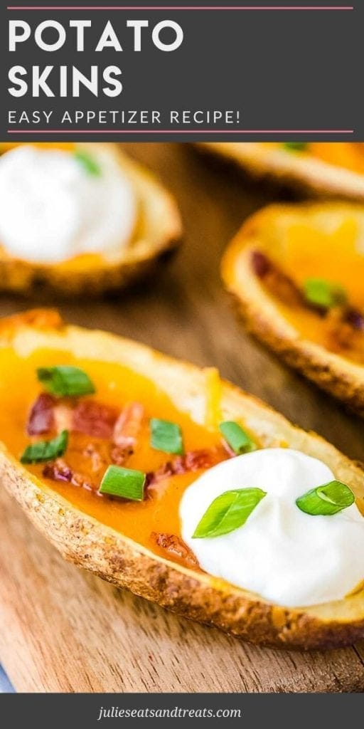 Potato skins topped with cheese, bacon, sour cream, and chives on a cutting board