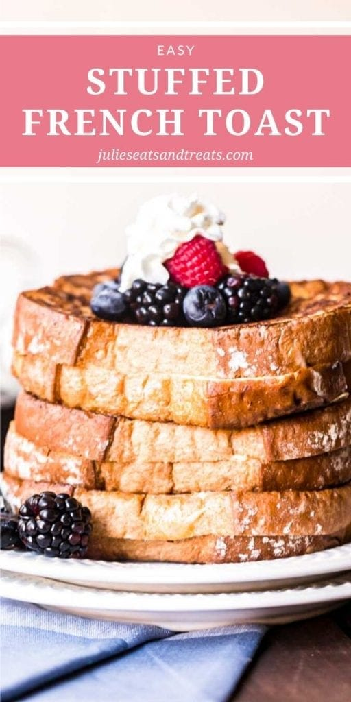 Stack of stuffed french toast topped with whipped cream and berries on a white plate