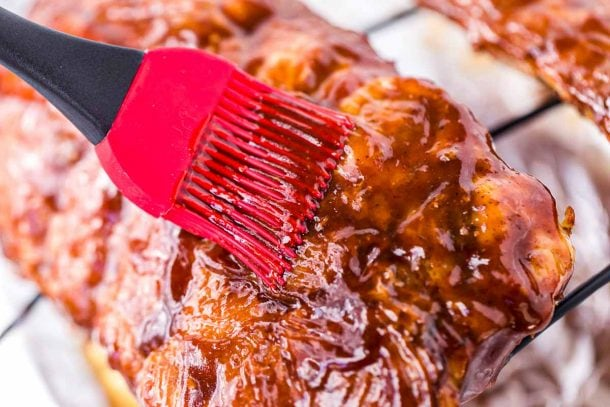 Ribs being brushed with BBQ Sauce