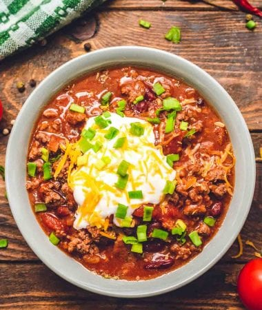 Bowl of Instant Pot Chili topped with sour cream, shredded cheese, and chives