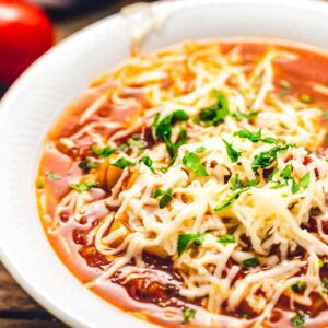 White bowl of lasagna soup topped with shredded cheese.