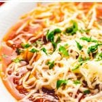 Pressure cooker lasagna soup in a white bowl topped with shredded cheese