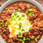 chili in a bowl topped with sour cream, shredded cheese, and chives