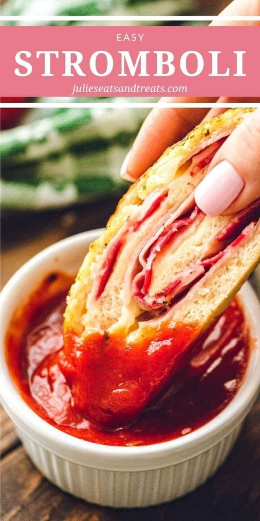 Hand dipping a slice of stromboli into marinara sauce