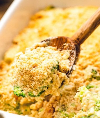 Wooden spoon scooping broccoli casserole out of a white baking dish