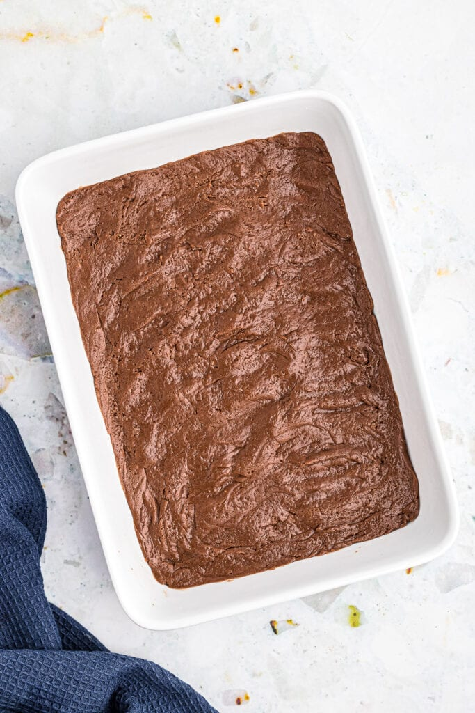 Overhead image of white baking dish with a thin layer of chocolate brownie mix on bottom before baking