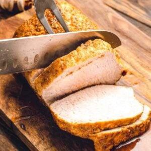 Pork loin being sliced on a wood cutting board