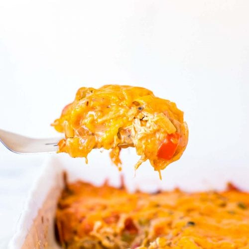 a bite of king ranch casserole on a fork over the top of the casserole