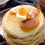 Syrup being poured over a tall stack of pancakes with butter and black berries