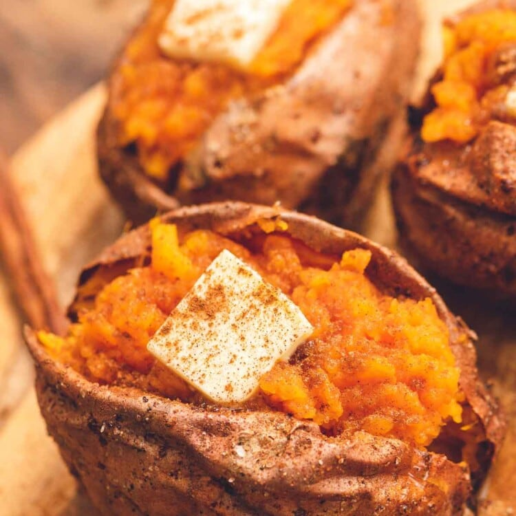 Air Fryer Baked Sweet Potato cut open and topped with butter and sprinkled with cinnamon