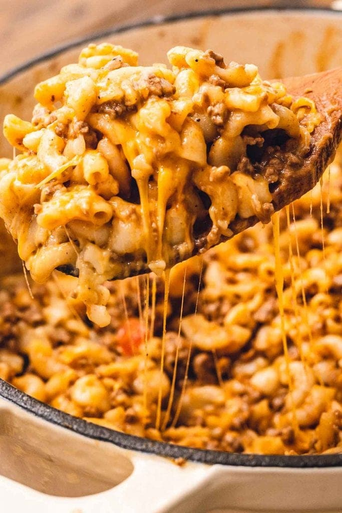 Wooden spoon with cheesy hamburger helper over a dutch oven