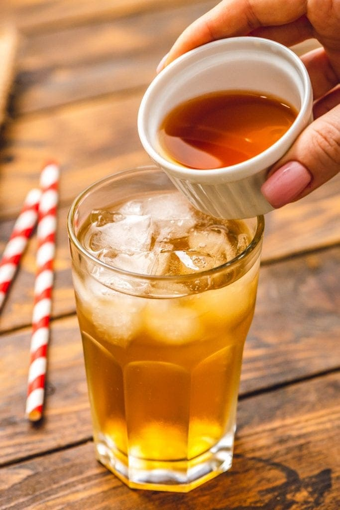 Dish pouring iced tea into a glass with lemonade and ice