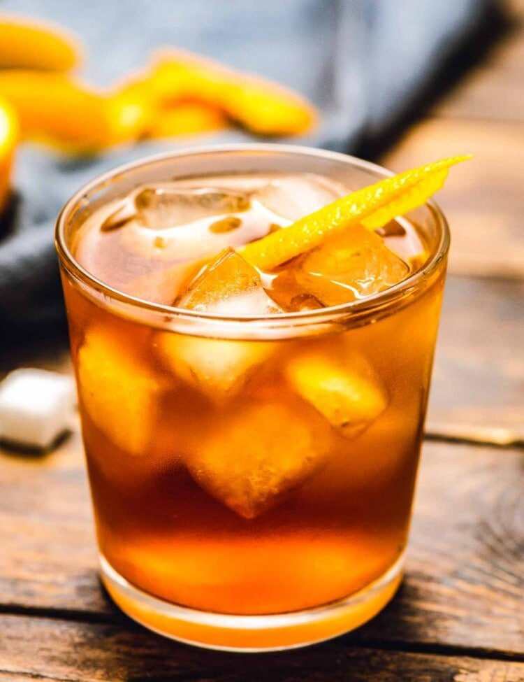 Glass with old fashioned cocktail ice and orange peel