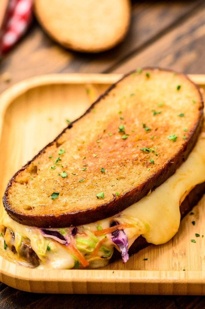Wood platter with sandwich showing melted cheese and coleslaw
