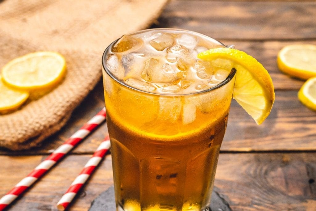 Glass with Spiked Arnold Palmer and garnished with lemon slice