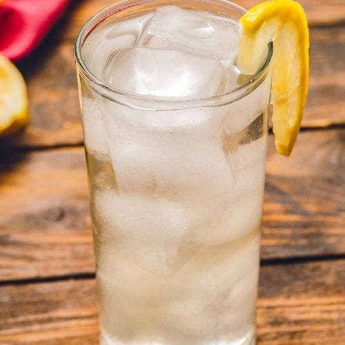 Tom collins in glass with ice and a lemon slice