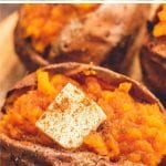 Baked sweet potatoes split open with a pad of butter in the center and sprinkled with cinnamon