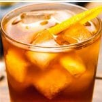Old fashioned drink in a clear glass with ice cubes and an orange rind