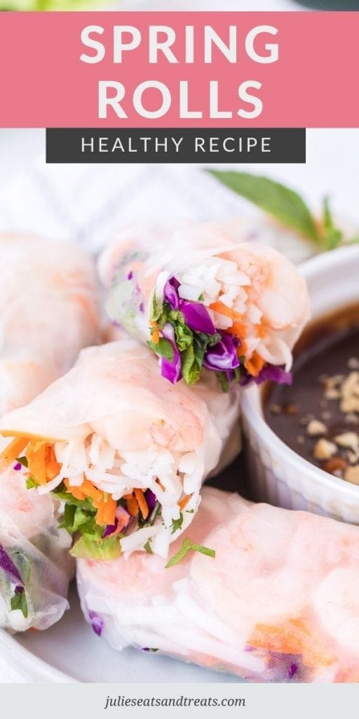 Spring Rolls cut in half and stacked with a bowl of sauce on the side