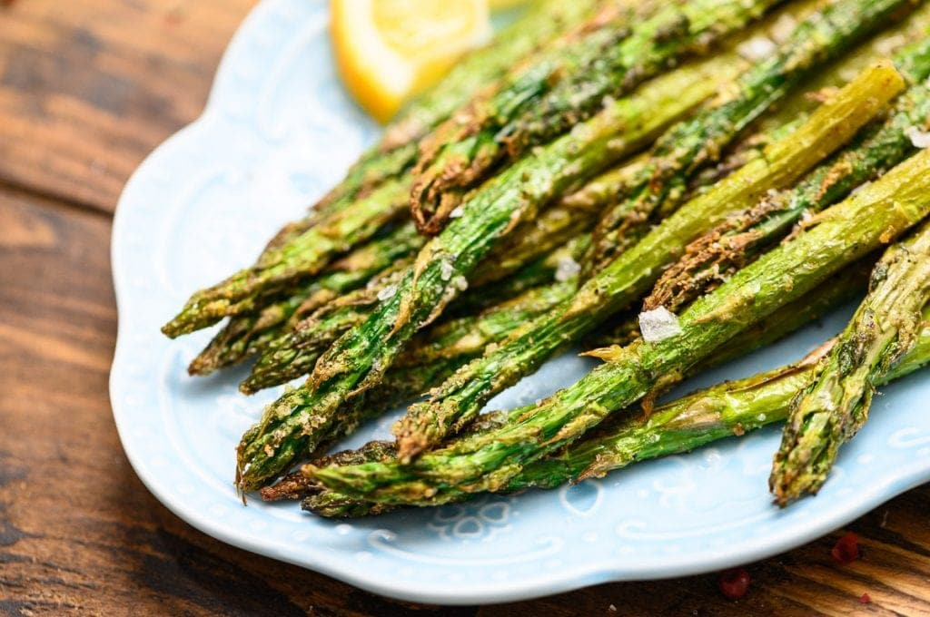 Roasted Asparagus on blue plate with lemon slices for garnish