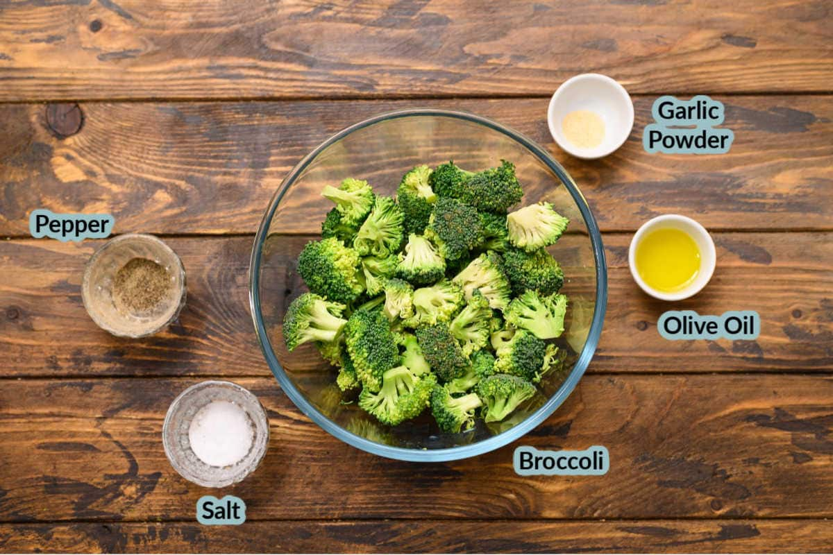 Wood background with ingredients to make air fryer broccoli