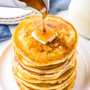 White plate with stack of pancakes and slab of butter on top with syrup being poured